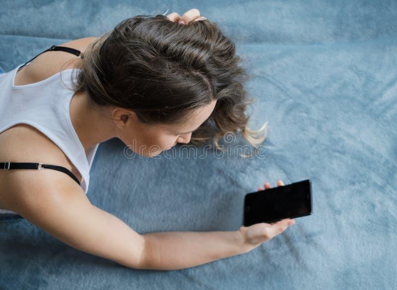 年轻人相当白肤金发的卷发妇女使用一个智能手机并且说谎 免版税库存图片