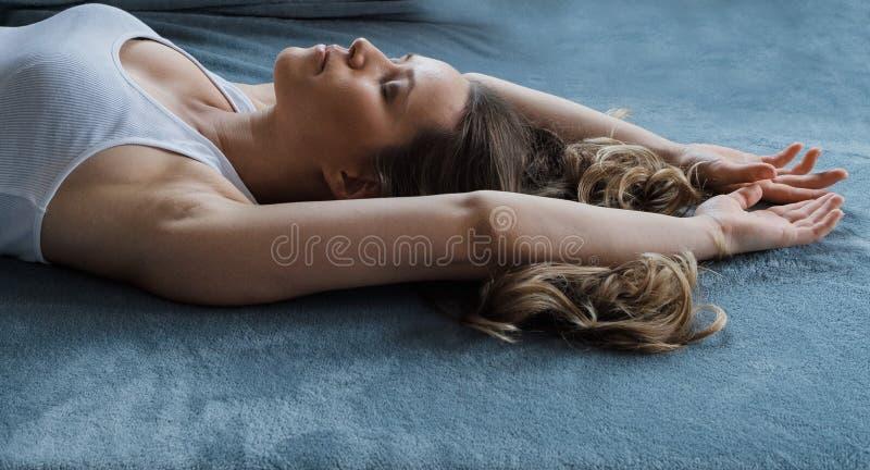 年轻人相当白肤金发的卷发妇女在一张蓝色床上睡觉 免版税库存照片