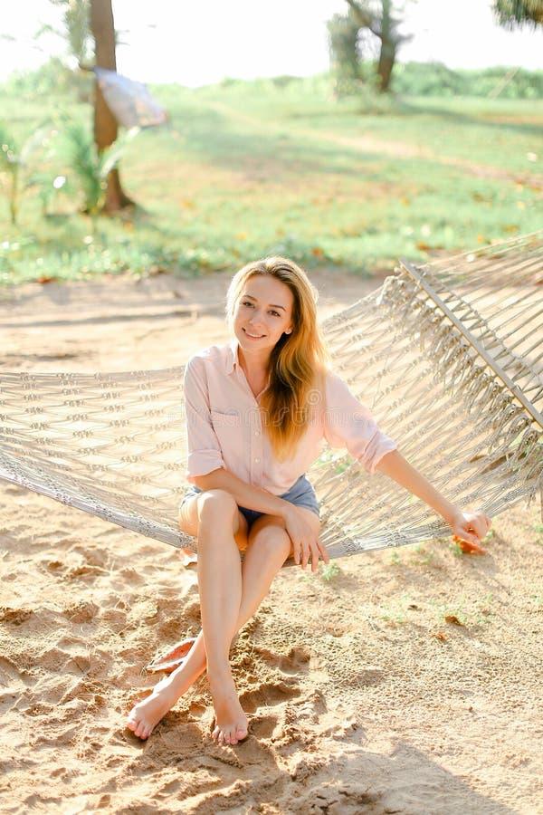 年轻人相当白肤金发的女性坐柳条吊床,沙子背景 免版税库存照片