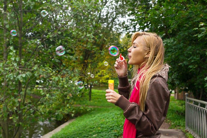 年轻人相当白肤金发的妇女吹的肥皂泡在公园 图库摄影