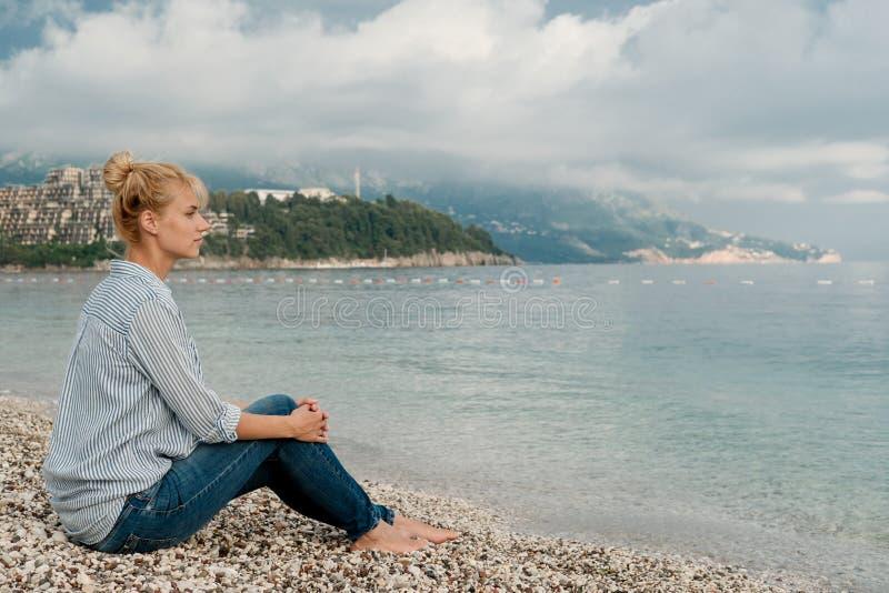 年轻人相当白肤金发的妇女画象镶边衬衣的在海b 库存照片