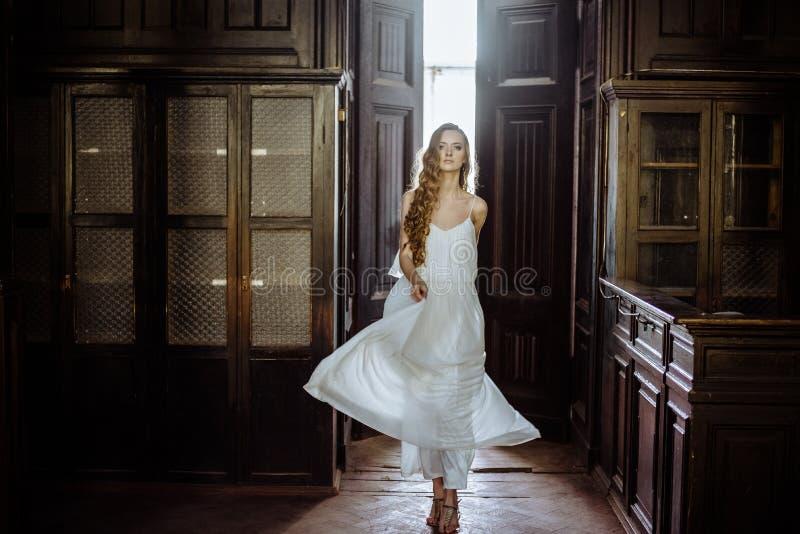 年轻人相当逗人喜爱的女孩室内夏天画象  摆在木内阁,伤痕老塑象里面的童话门旁边的美丽的妇女 库存图片