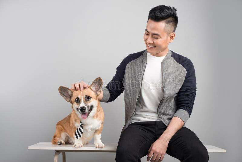 年轻人看一条小狗狗并且保留在狗` s的一只手 免版税图库摄影