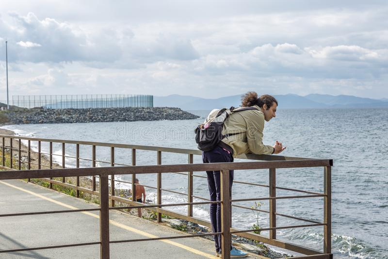 年轻人看从码头的海 美好的镇静海景 库存照片