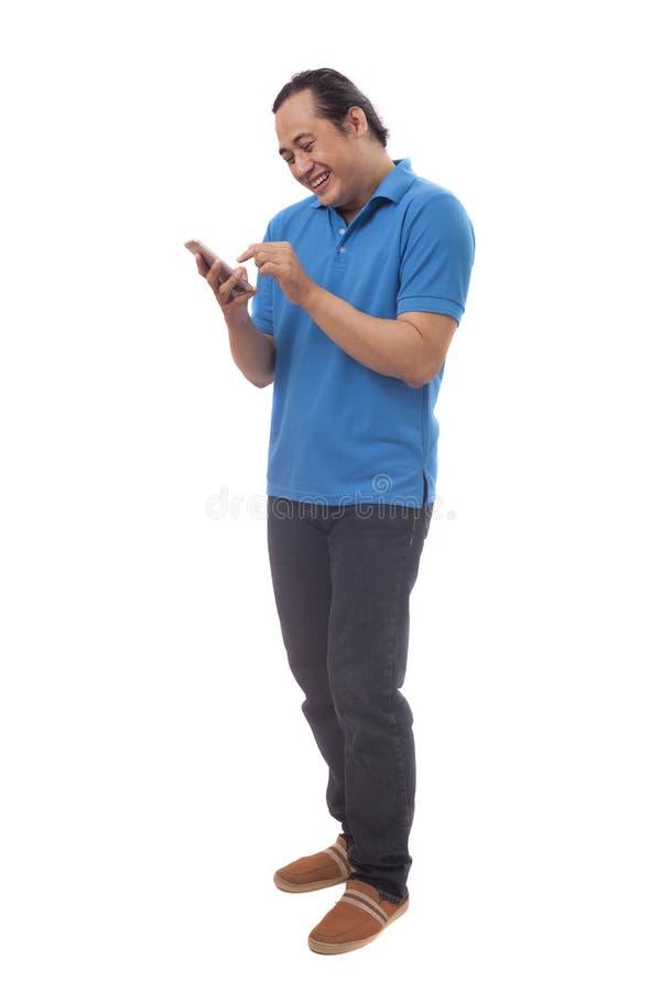 年轻人短信的读书聊天在他的电话的,微笑愉快 免版税库存照片