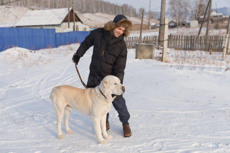年轻人站立与在一条冬天街道上的一条大狗在村庄房子的背景中 库存图片