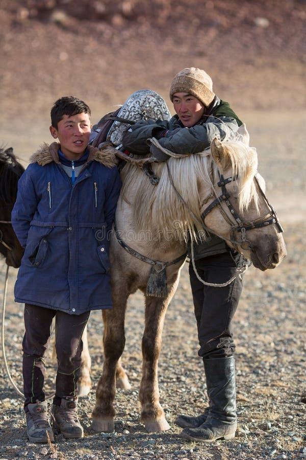 年轻人站立在他们的马附近的老鹰猎人在狩猎期间在瓦剌山沙漠  免版税库存照片