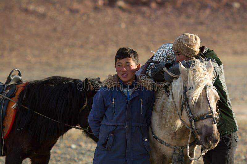 年轻人站立在他们的马附近的老鹰猎人在狩猎期间在瓦剌山沙漠  库存照片