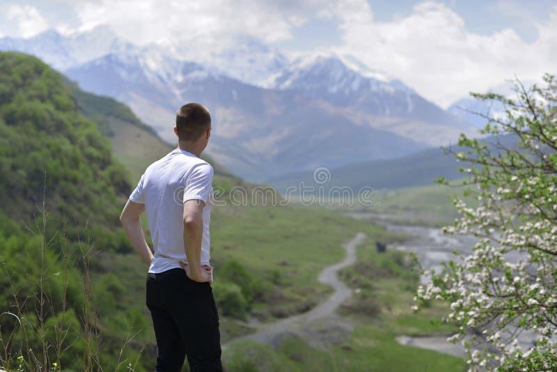 年轻人站立高在山在开花的树旁边和神色在谷和积雪覆盖的山 免版税图库摄影