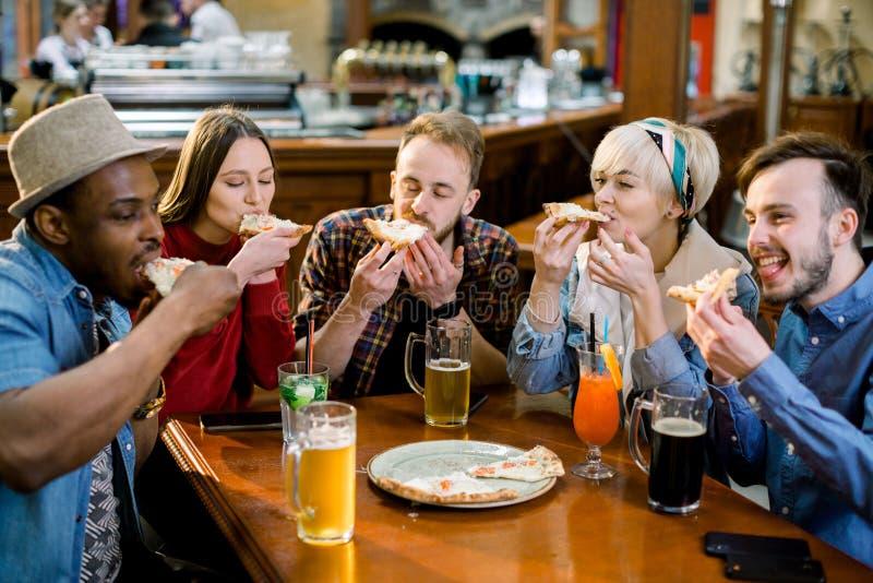 年轻人笑五的人吃比萨和,当坐在便当餐馆时 享受一会儿的小组朋友 库存图片