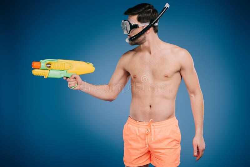 年轻人简而言之和潜水掩没拿着水枪 库存图片