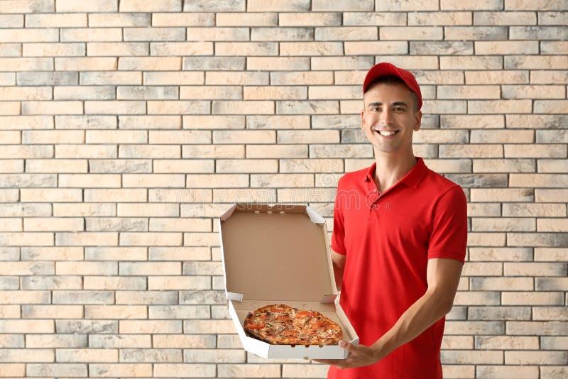 年轻人藏品箱子用鲜美比萨对砖墙 e 图库摄影