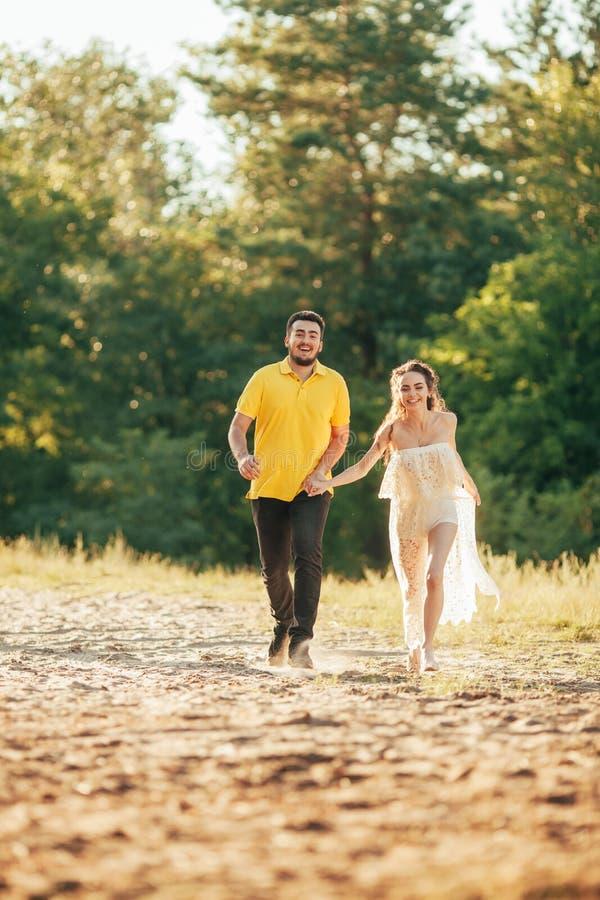 年轻人被迷恋的夫妇在森林里举行手和奔跑 库存图片
