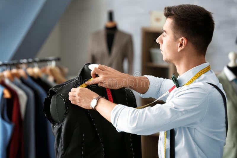 年轻人裁缝与衣服的夹克一起使用. 布料, 成人.