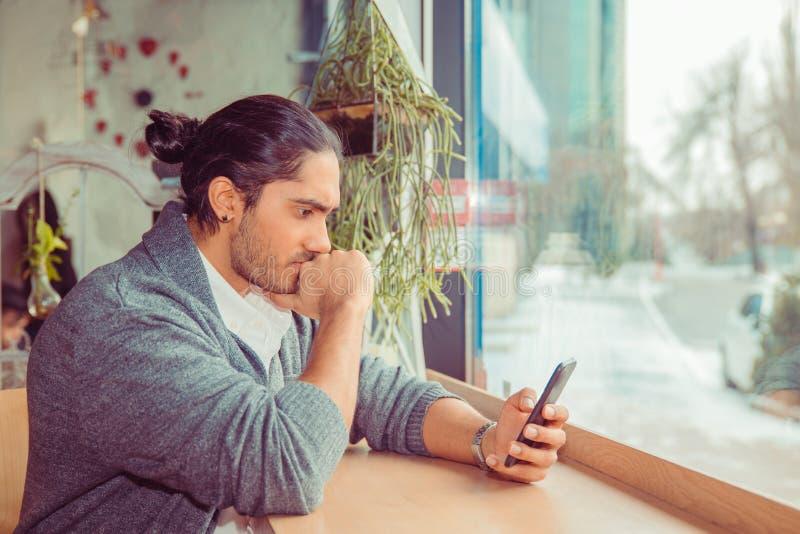 年轻人观看的智能手机和咬住的拳头在担心的表示 免版税库存照片