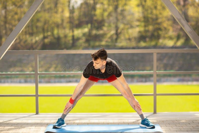 年轻人训练瑜伽户外 运动的人在一张蓝色瑜伽席子做伸展运动,在运动场 库存照片