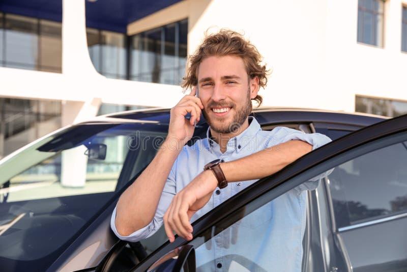 年轻人谈话在电话在现代汽车附近 库存照片