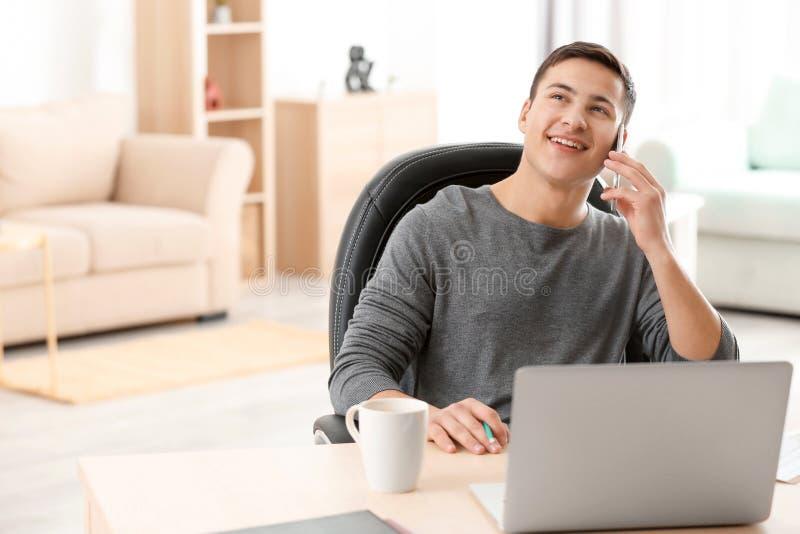 年轻人谈话在电话,当与膝上型计算机一起使用在家庭办公室时 图库摄影
