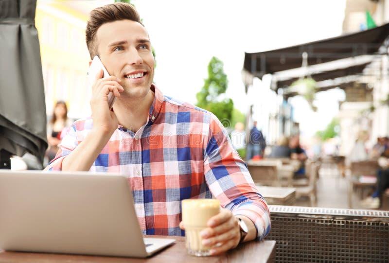 年轻人谈话在电话,当与膝上型计算机一起使用时 免版税图库摄影