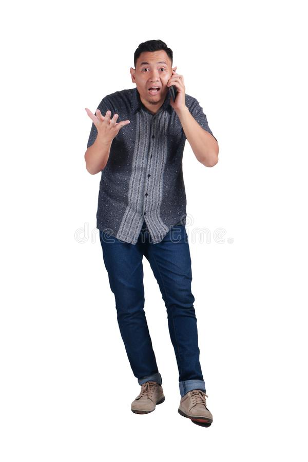 年轻人谈话在电话,震惊担心的表示 库存图片