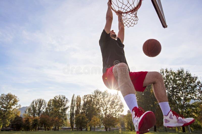 年轻人跳跃,在街上打篮球, 城市真迹 库存照片