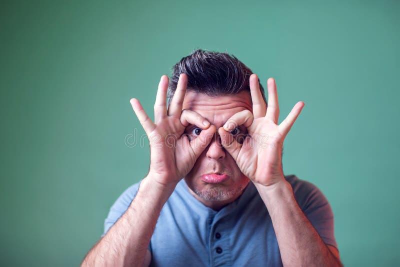 年轻人陈列与手指的猫头鹰标志 做滑稽的鬼脸 有一心情 人们,情感,生活方式 图库摄影