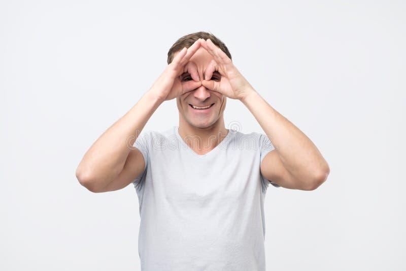 年轻人陈列与手指的猫头鹰标志 做滑稽的鬼脸 免版税库存图片