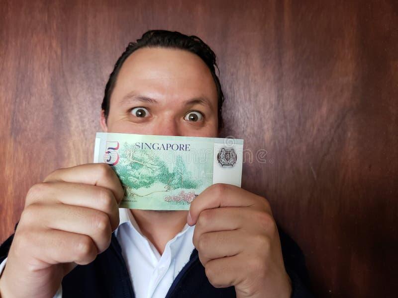 年轻人陈列和拿着五美元新加坡钞票  免版税图库摄影