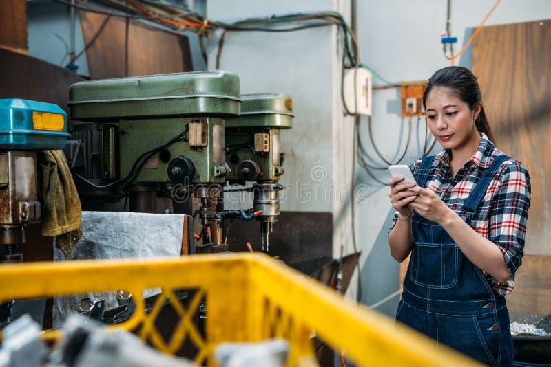 年轻人零件工厂女职工用途手机 库存图片