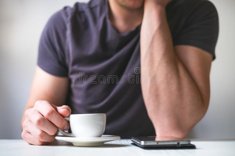 年轻人饮用的早晨咖啡和拿着手机 背景中断咖啡新月形面包杯子甜点 供以人员拿着杯子新鲜的烤咖啡和看t 库存图片