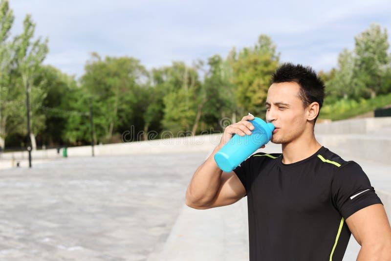 年轻人饮用的蛋白质震动 库存图片