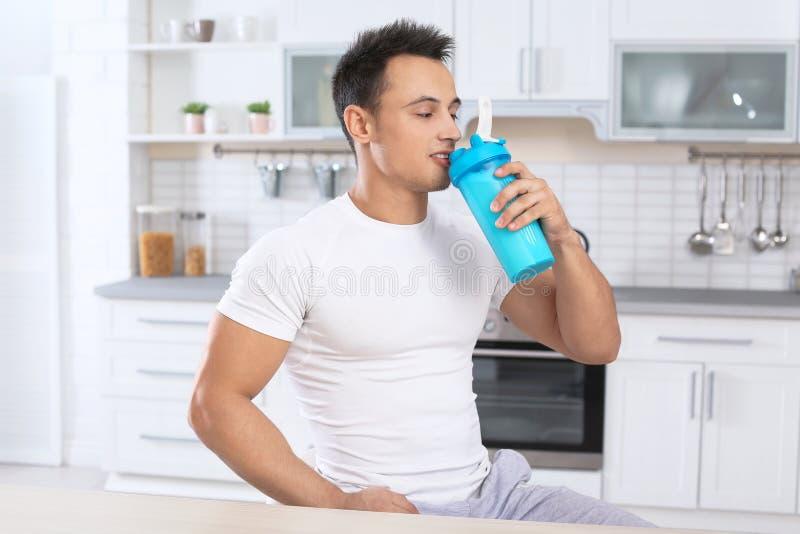 年轻人饮用的蛋白质震动 免版税库存图片