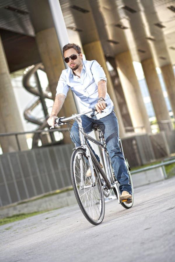 年轻人骑马自行车 免版税库存照片