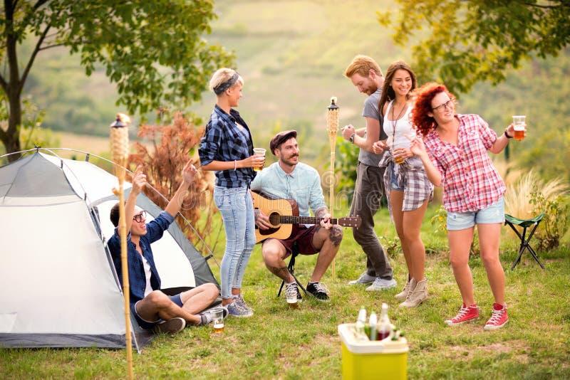 年轻人高兴和与吉他和啤酒的跳舞 免版税库存图片