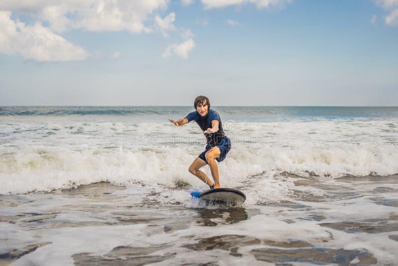 年轻人,初学者冲浪者在B的海泡沫学会冲浪 库存图片