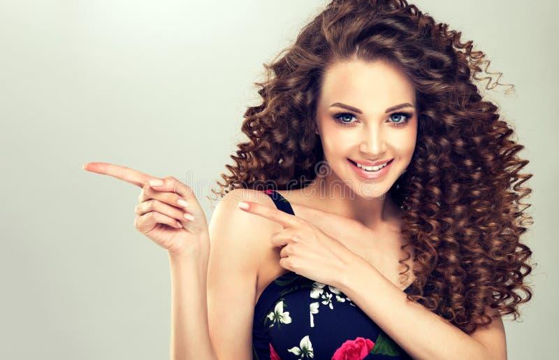 年轻人,宽微笑的棕色毛发的妇女指向得在旁边 广告的姿态 库存图片