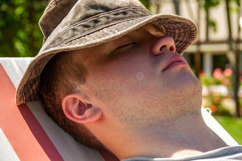 年轻人,少年,学生,特写镜头在帽子坐轻便折叠躺椅和休息 休息的概念,放松,休息 库存图片