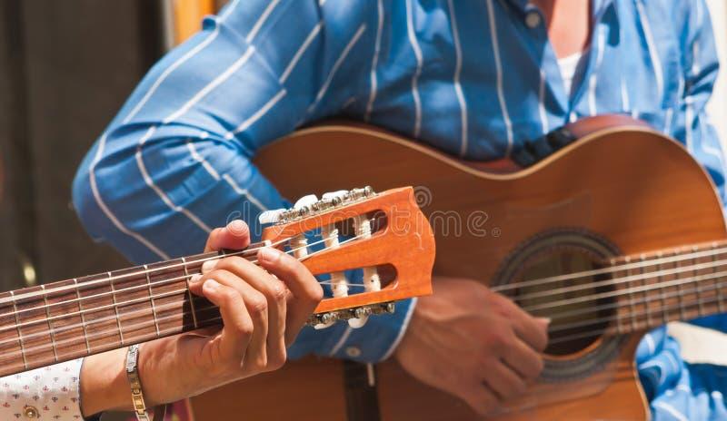 年轻人` s在马德里,西班牙递弹一把吉他 库存图片