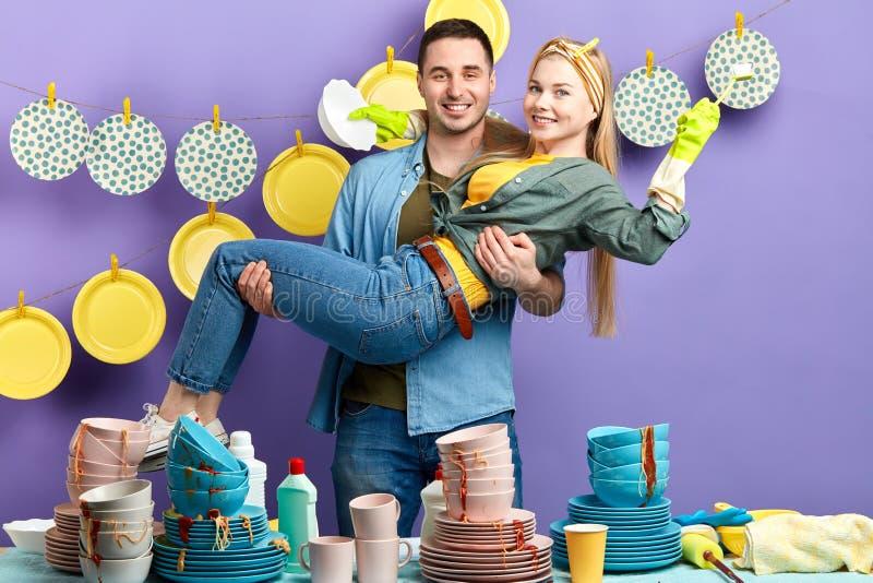 年轻令人敬畏的家庭获得乐趣在厨房屋子 图库摄影