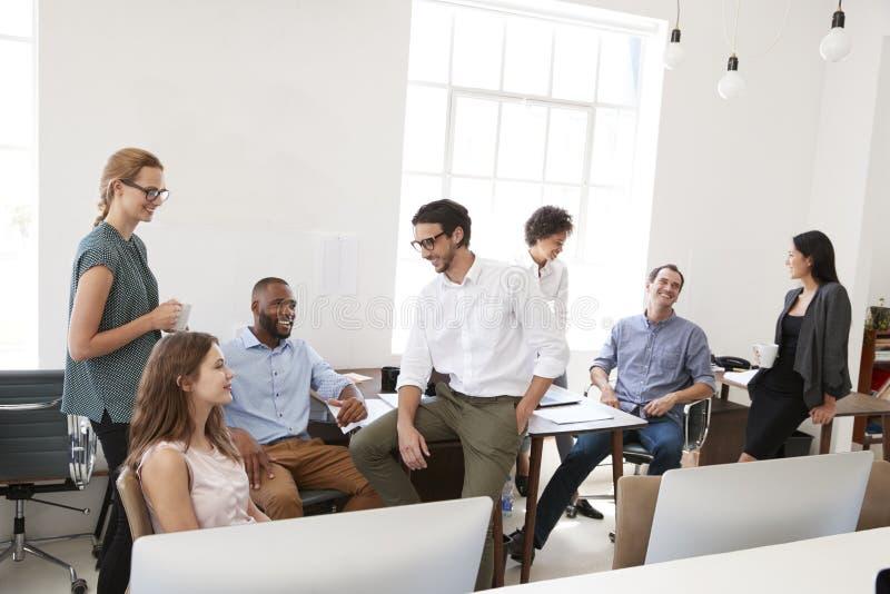 年轻企业同事在偶然会议上在他们的办公室 图库摄影