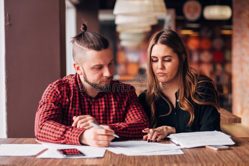 年轻企业家做了在咖啡馆的一个成交,签署文件 免版税库存图片
