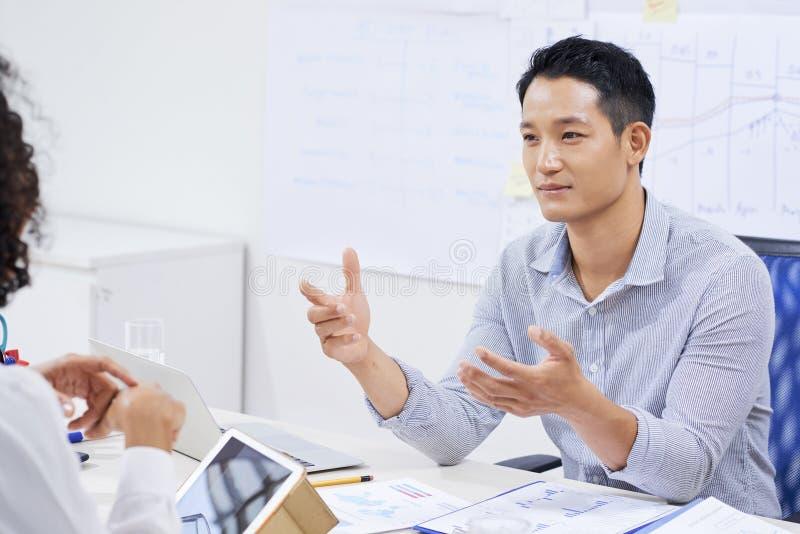 年轻企业家谈话与同事 免版税库存照片