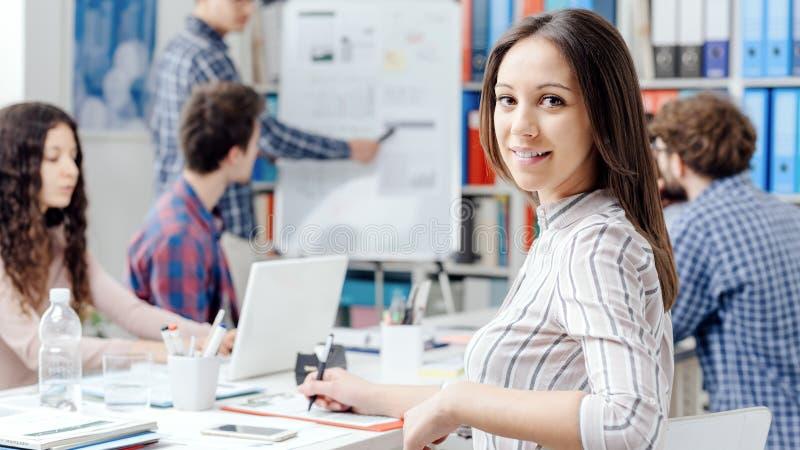 年轻企业队和女孩微笑 免版税库存照片