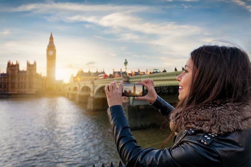 年轻伦敦游人是与她的手机的照相从大本钟在威斯敏斯特 免版税图库摄影