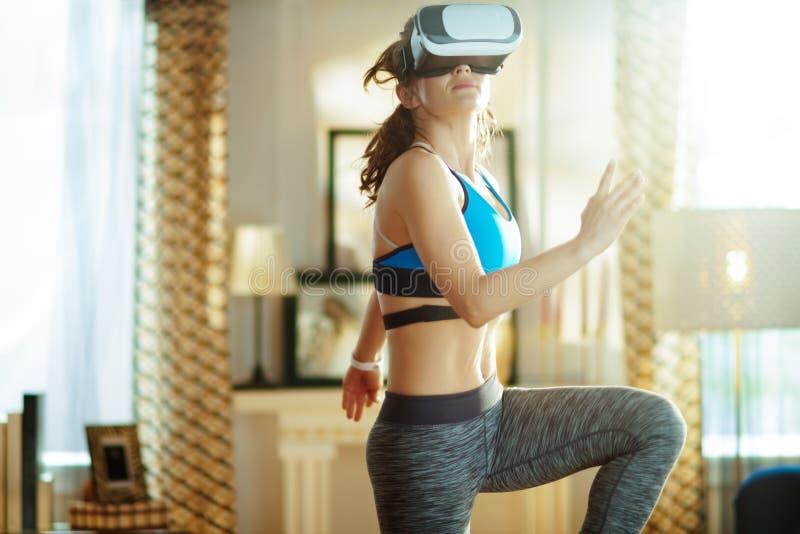年轻体育妇女在VR玻璃锻炼的现代客厅 免版税库存照片