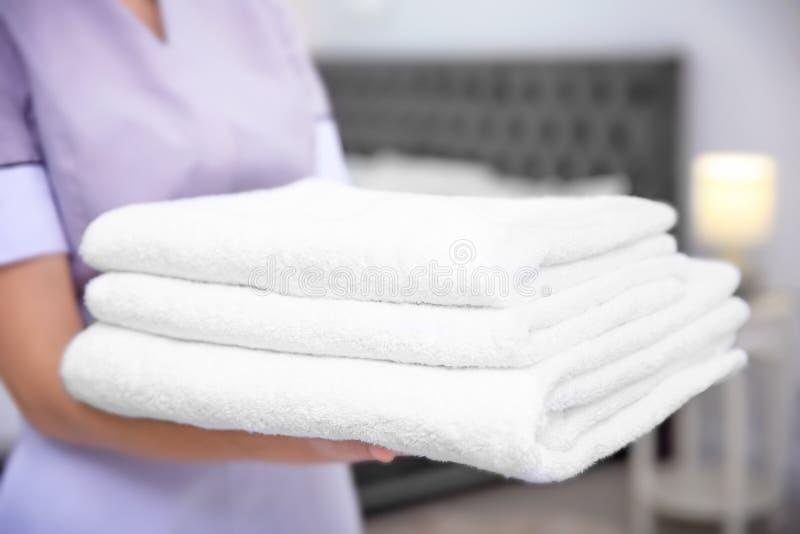 年轻佣人藏品堆毛巾在旅馆客房 免版税库存图片