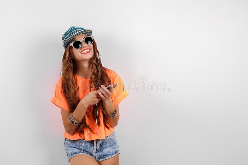 年轻佩带在盖帽的太阳镜的行家美丽的妇女和橙色在耳机的T恤杉听的音乐临近白色 库存照片