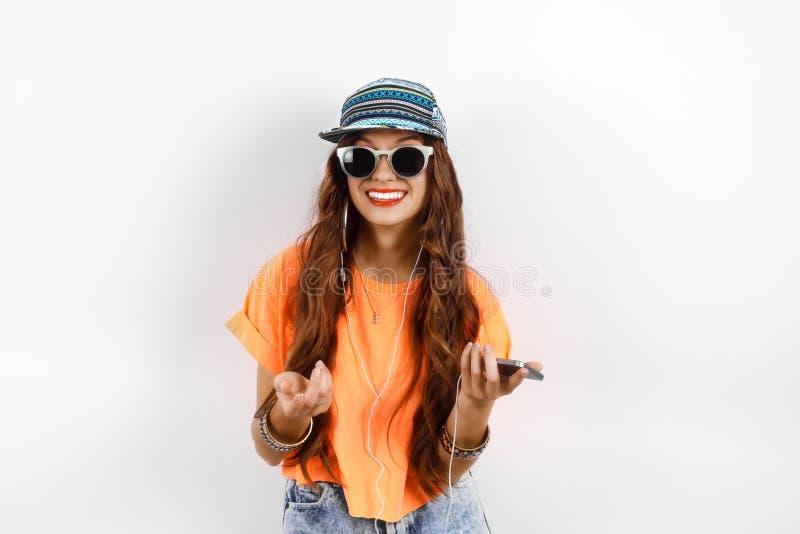 年轻佩带在盖帽的太阳镜的行家美丽的妇女和橙色在耳机的T恤杉听的音乐临近白色 库存图片