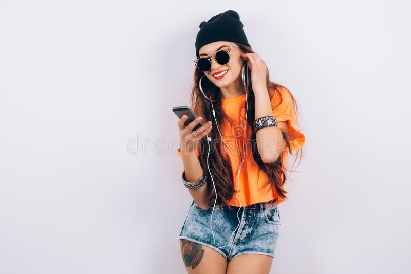 年轻佩带在黑帽会议和橙色T恤杉听的音乐的太阳镜的行家美丽的妇女在耳机近 免版税库存图片