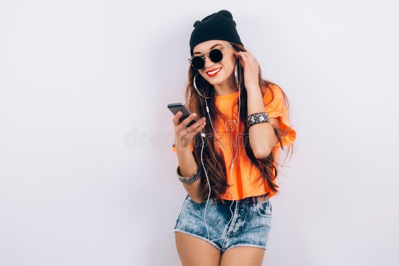 年轻佩带在黑帽会议和橙色T恤杉听的音乐的太阳镜的行家美丽的妇女在耳机近 库存图片